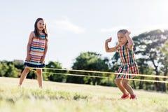演奏中国跳绳的两个女孩在公园 免版税库存图片
