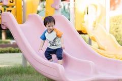 演奏乐趣的小男孩在操场 免版税库存照片