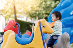 演奏乐趣的小男孩在操场 免版税图库摄影