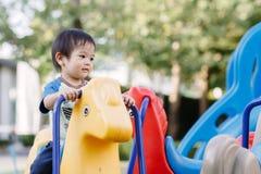 演奏乐趣的小男孩在操场 免版税库存图片