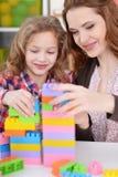 演奏五颜六色的塑料块的女孩和她的母亲 免版税库存图片