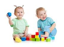 演奏五颜六色的玩具的滑稽的孩子隔绝在白色 库存照片