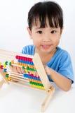 演奏五颜六色的算盘的亚裔矮小的中国女孩 免版税库存照片