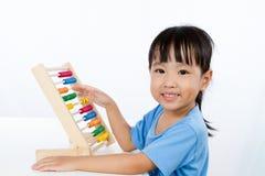 演奏五颜六色的算盘的亚裔矮小的中国女孩 免版税库存图片