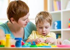演奏五颜六色的黏土的儿童男孩和母亲戏弄 免版税库存图片