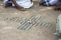 演奏传统印地安boardgame Ashta Chamma,古老比赛Chowka Bhara的另一个名字的小组男人和妇女 免版税库存图片