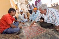 演奏传统印地安boardgame Ashta Chamma,古老比赛Chowka Bhara的另一个名字的严肃的人 免版税图库摄影