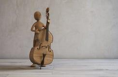 演奏低音提琴的音乐家在一间现代演播室屋子 免版税库存图片