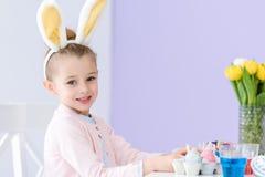 演奏佩带的兔宝宝耳朵的儿童女孩由与复活节的桌 免版税图库摄影