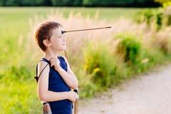 演奏使用与弓和玩具箭头的男孩 免版税库存图片