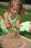 演奏俏丽的沙子年轻人的女孩头发 免版税库存照片
