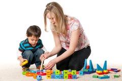 演奏儿子的地毯母亲 免版税库存照片