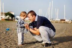 演奏儿子的海滩父亲 免版税图库摄影
