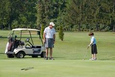 演奏儿子的父亲高尔夫球 免版税库存图片