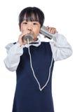 演奏减速火箭的锡罐电话的亚裔中国小女孩 库存图片