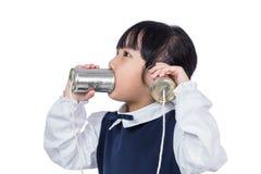 演奏减速火箭的锡罐电话的亚裔中国小女孩 免版税图库摄影