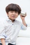 演奏减速火箭的锡罐电话的亚裔中国小男孩 免版税库存照片