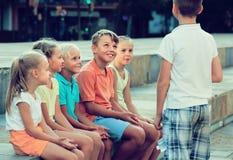 演奏凭动作猜字谜游戏的微笑的孩子户外 免版税图库摄影