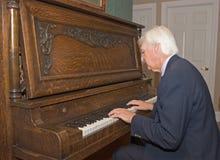 演奏前辈的人钢琴 免版税库存照片