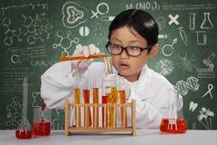 演奏化学制品的男小学生在实验室 库存照片