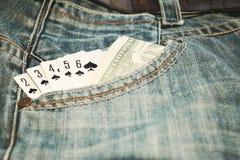 演奏卡片同花顺和金钱在斜纹布口袋 免版税库存照片