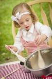 演奏厨师烹调的可爱的小女孩 免版税库存图片