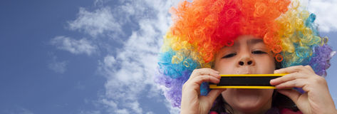 演奏口琴的孩子小丑 免版税库存照片