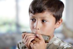 演奏口琴的男孩 免版税库存照片