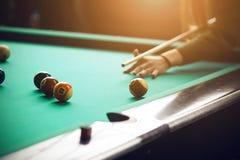 演奏台球的一件绿色毛线衣的一个女孩 免版税库存照片