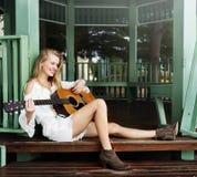 演奏吉他休闲爱好概念的妇女 免版税图库摄影