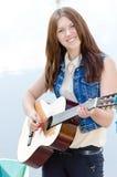 演奏吉他愉快微笑的年轻美丽的女孩 库存照片