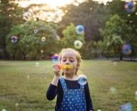 演奏吹的泡影乐趣的幼儿园女小学生 图库摄影