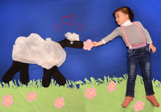 演奏和喂养羊羔的孩子 免版税库存照片