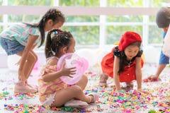 演奏和投掷纸和气球在孩子党的孩子 免版税库存照片