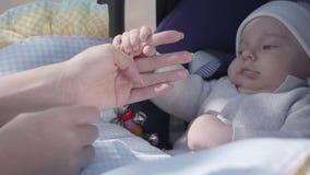 演奏和照顾她支架的新出生的可爱宝贝的年轻愉快的母亲在一个好春日 影视素材