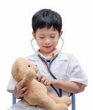 演奏和治疗熊玩具的年轻亚裔医生男孩 免版税库存照片