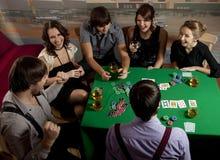 演奏啤牌年轻人的人们 免版税库存图片