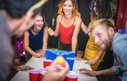 演奏啤酒pong在青年招待所-时间与被拔去乐趣的背包徒步旅行者的旅行概念的年轻朋友在宾馆 免版税库存图片