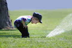 演奏喷水隆头的男孩 免版税库存图片