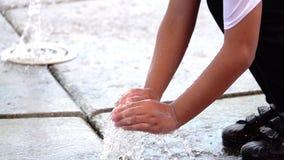 演奏喷泉水慢动作的亚洲孩子的手 影视素材