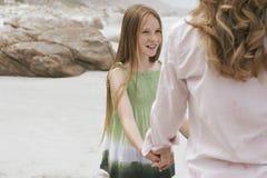 演奏圆环的女孩在玫瑰色附近与海滩的母亲 库存图片