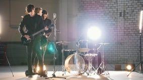 ?? 演奏在一明亮hargar的一群年轻人摇滚音乐 股票视频