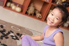 演奏在地板上的逗人喜爱的小女孩多米诺。 免版税库存图片