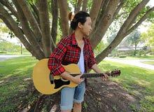 演奏在声学吉他的年轻轻松的人广角射击音乐在美好的自然背景中 图库摄影