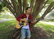 演奏在声学吉他的年轻轻松的人广角射击音乐在美好的自然背景中 免版税图库摄影