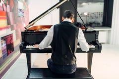 演奏在大平台钢琴的男性钢琴演奏家构成 图库摄影