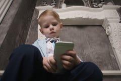 演奏在床上的男孩智能手机 观看的智能手机 孩子用途电话和戏剧比赛 儿童用途机动性 上瘾的比赛和 库存照片
