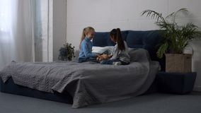 演奏在床上的逗人喜爱的多种族女孩玩具 股票视频