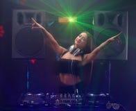 演奏在搅拌器的音乐和跳舞与光束的性感的妇女dj 免版税库存图片