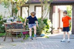 演奏在操场的两个一点学校和幼儿园孩子男孩跳房子 免版税库存图片